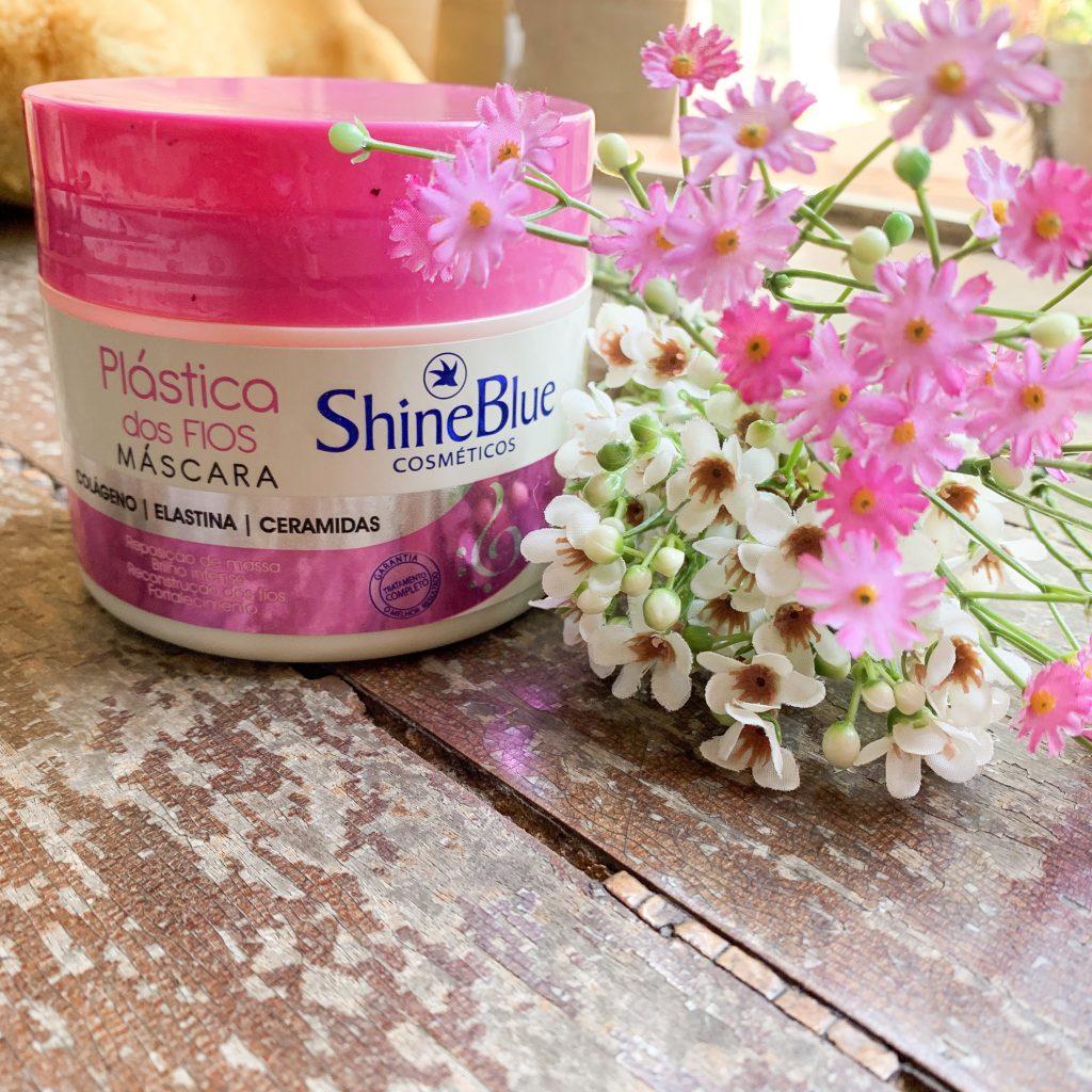 A foto mostra a máscara da linha Plástica dos Fios da Shine Blue. A embalagem é redonda, branca e tem a tampa rosa.