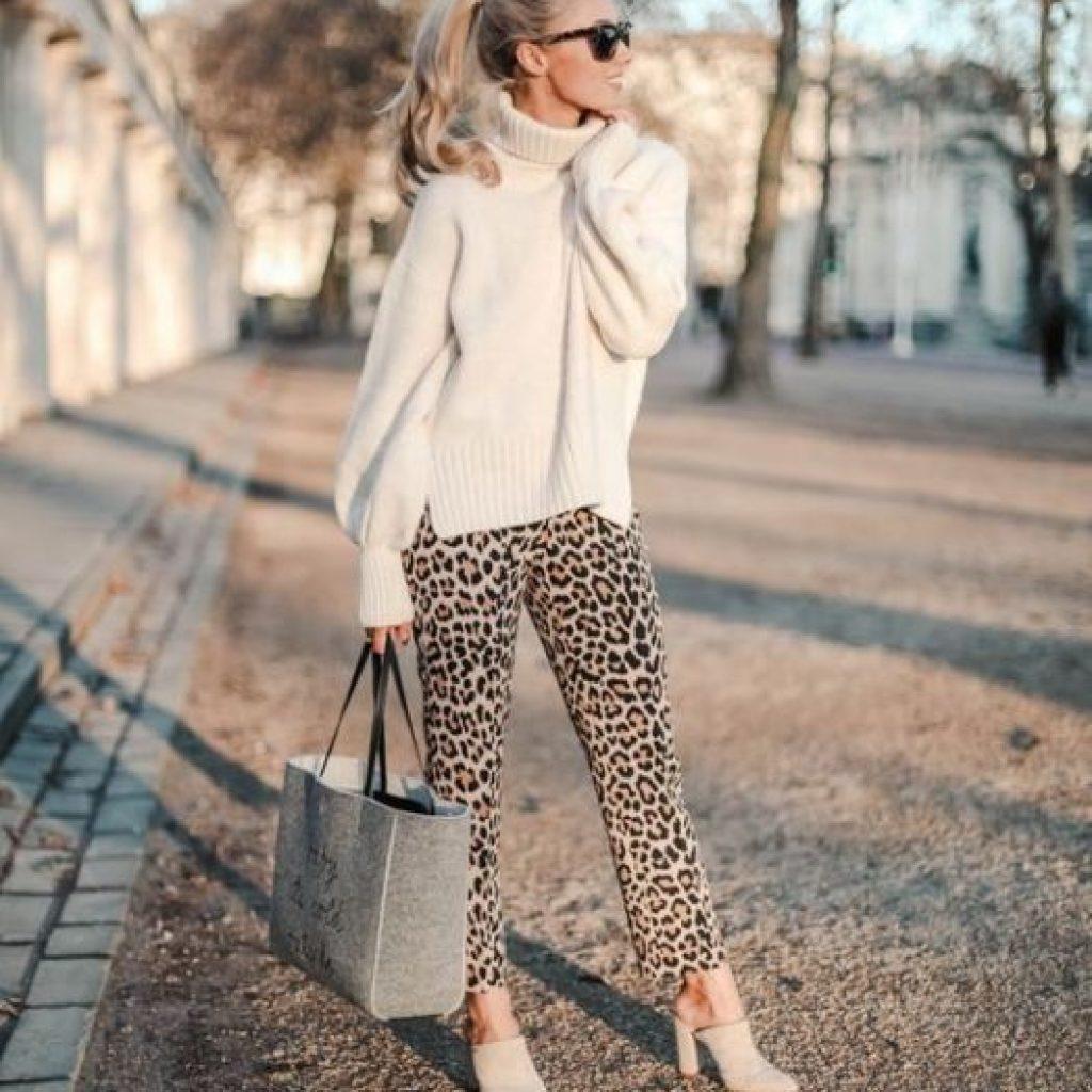 A foto mostra um look com animal print, tendência de inverno. Calça com estampa de onça e blusa gola alta.