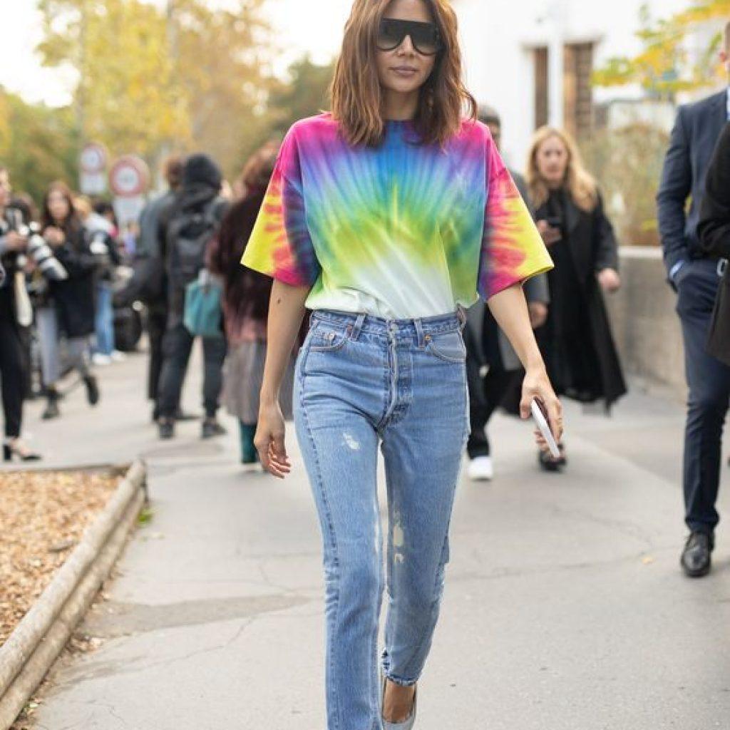 A foto mostra uma mulher com camiseta de estampa tie-dye, uma das tendências do verão 2020.