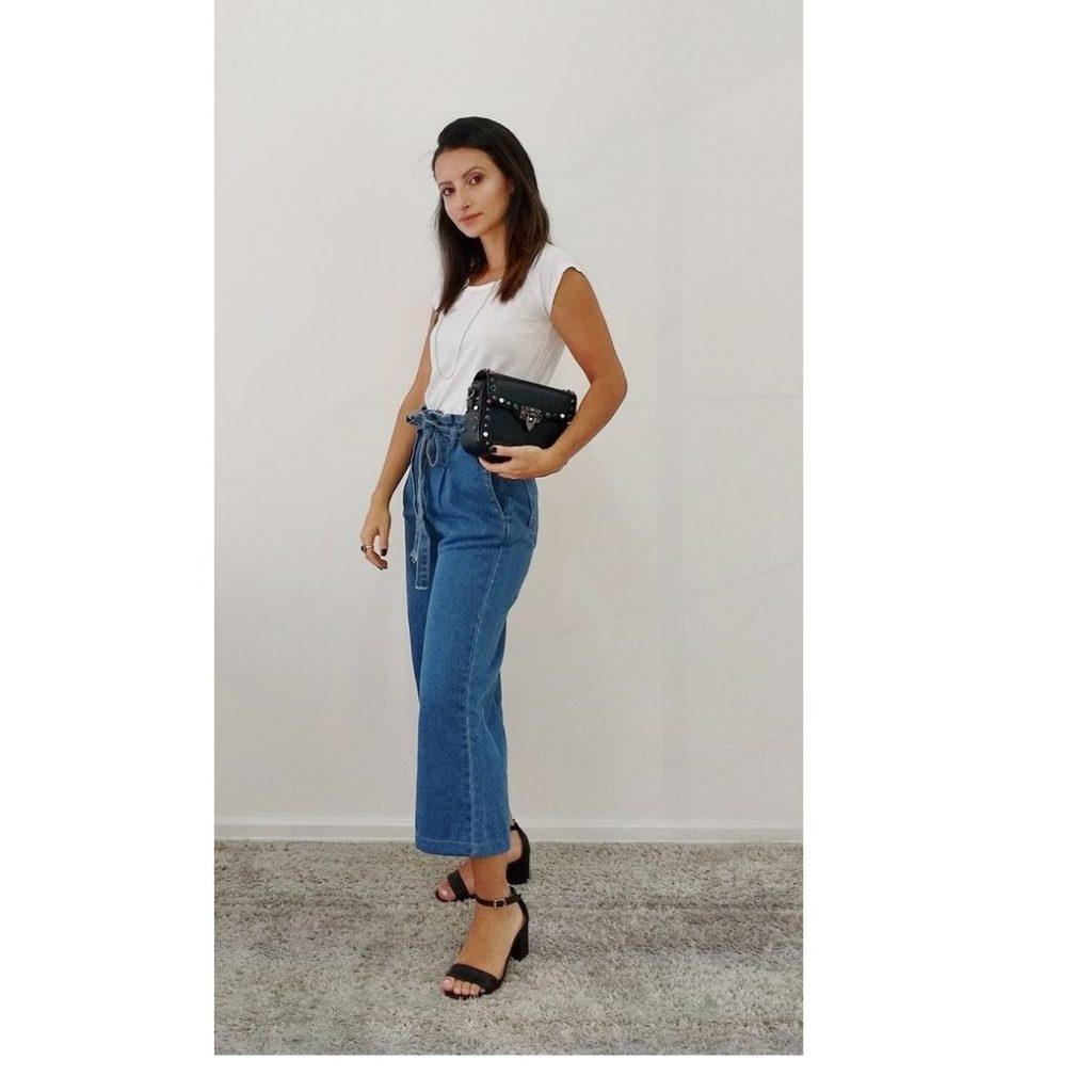 A foto mostra um look de calça jeans com sandália preta